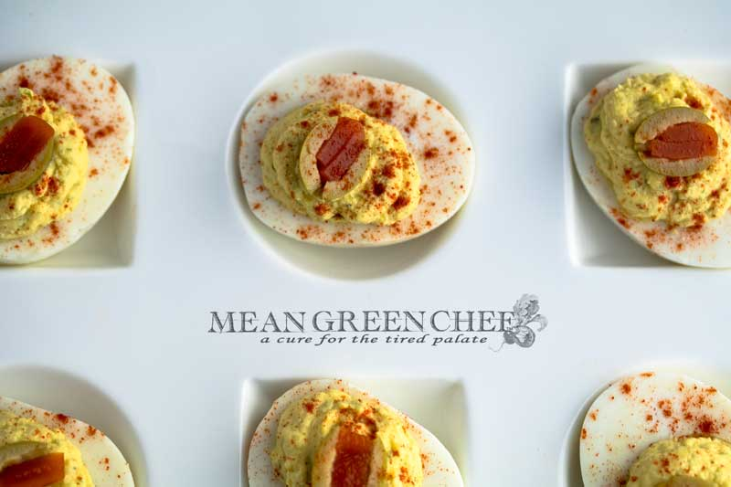 Classic Deviled Eggs on a large with platter with circle and square depressions for the eggs, sitting on a white cotton kitchen towel on an old blue wooden background. Mean Green Chef