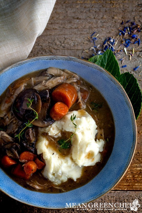 Coq Au Vin in a blue bowl on a wooden background