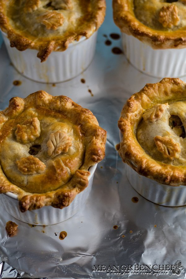 Overhead photo of four large double crust chicken pot pies in white ramekins on a baking sheet lined with foil. Mean Green Chef