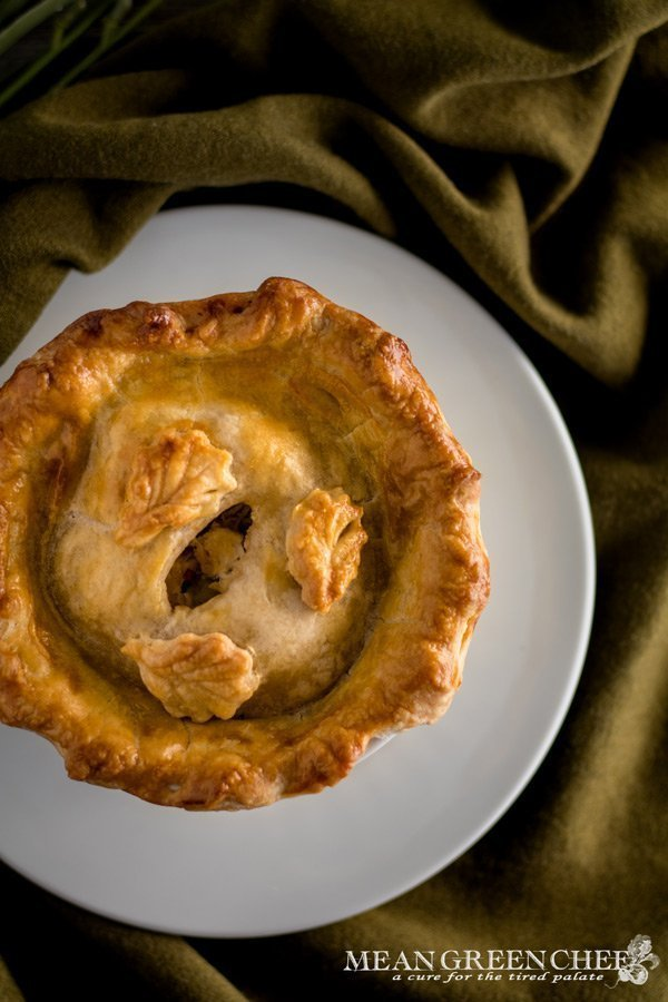 Overhead photo of a large double crust chicken pot pies in white ramekins on a green fabric background. Mean Green Chef