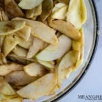Freshly sliced apples coated with apple pie spice for Caramel Apple Pie in a large glass bowl on a white marbled background. Mean Green Chef