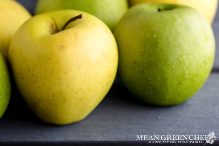 Granny Smith and Golden Delicious Apples on a gray wooden background. Mean Green Chef