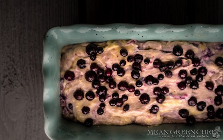 Overhead photo of Rustic Blueberry Banana Bread batter in a blue scalloped loaf pan on a gray wooden background. Mean Green Chef