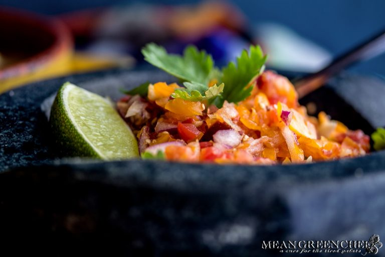 Mortar and pestle filled with fresh tomato salsa garnished with cilantro and fresh lime.