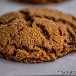 Freshly baked Best Ever Molasses Cookie close up showing crispyness of the outside of the cookie. Cooling on a piece of parchment paper on a baking sheet. Mean Green Chef