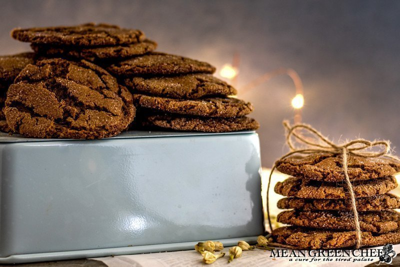 Stack of Molasses Cookies, tied with twine and sitting on newspaper that has been scattered with white flower buds. Mean Green Chef Best Ever Molasses Cookies