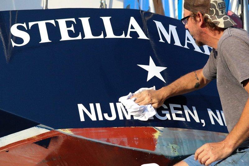 Craig Greven polishing Stella Maris his family sailboat.