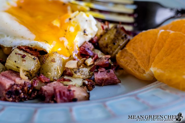 Overhead shot of Restaurant Style Corned Beef Hash topped with sunny side up eggs.