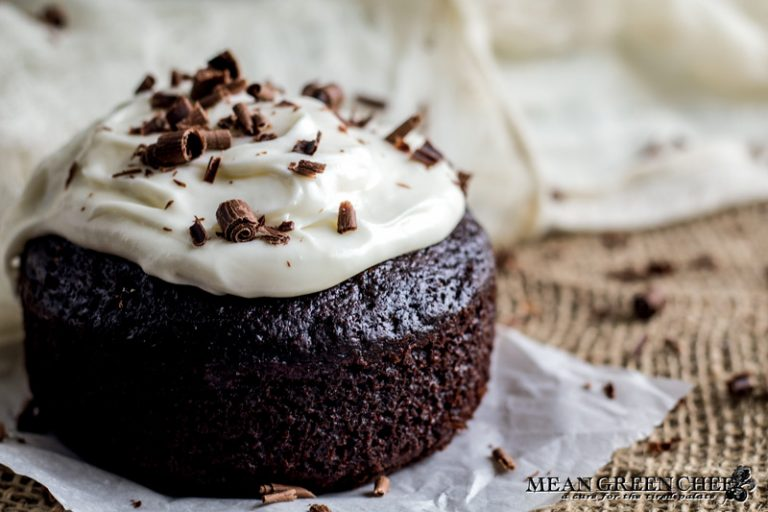 Side photo of Guinness Chocolate Cake with chocolate shavings sitting on parchment paper.