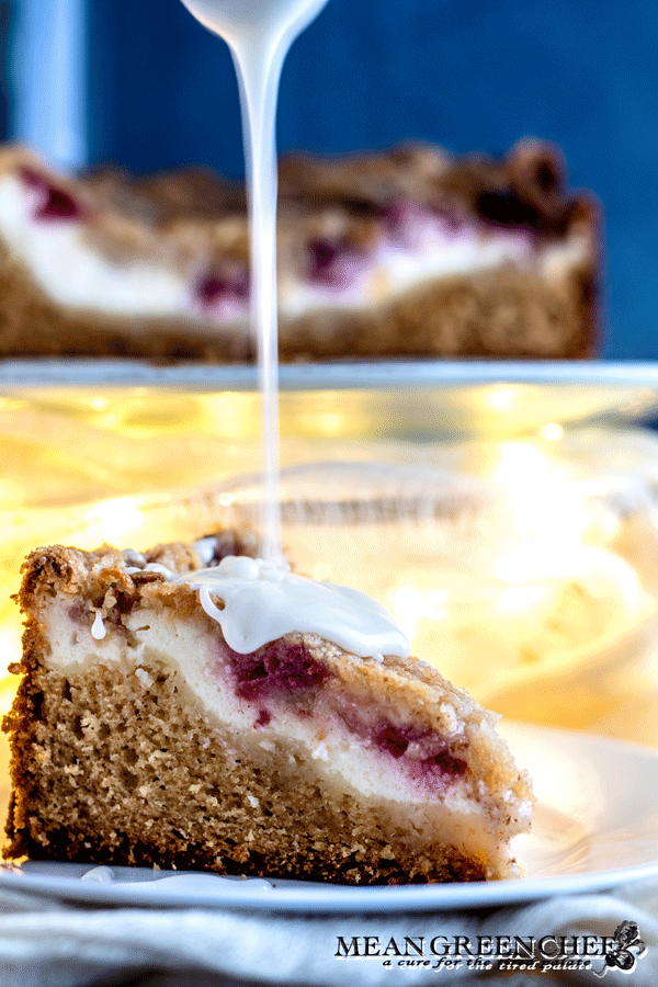 Side photo of Raspberry Coffee Cake with thick vanilla glaze being poured over top.