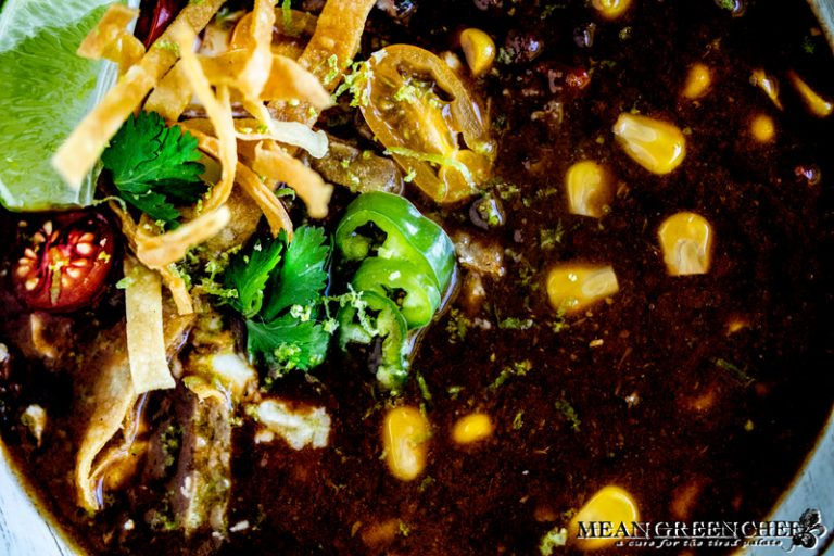 Close up of a bowl of Black Bean Soup garnished with crispy tortilla strips, jalapenos and cilantro.