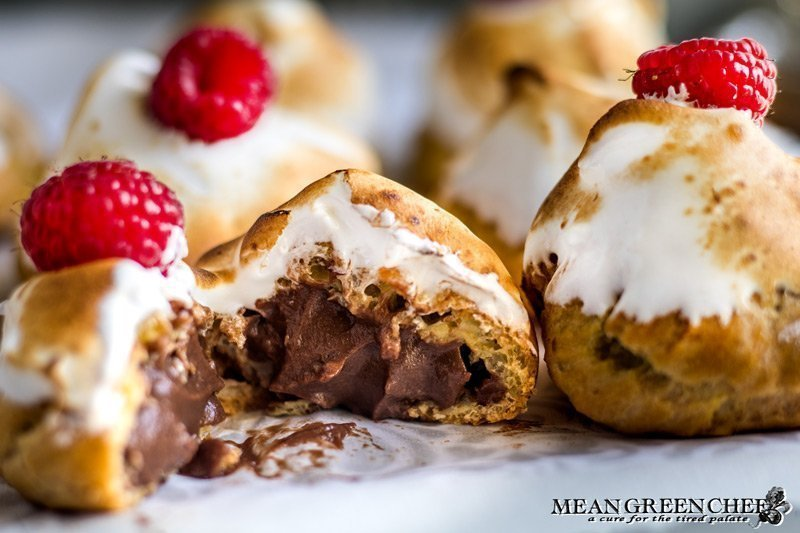Rich Chocolate Creme Patissiere Pastry Cream in cream puffs with Swiss Meringue and red raspberries on top.
