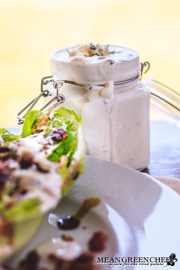 Buttermilk Blue Cheese Dressing in a glass jar next to a wedge salad.