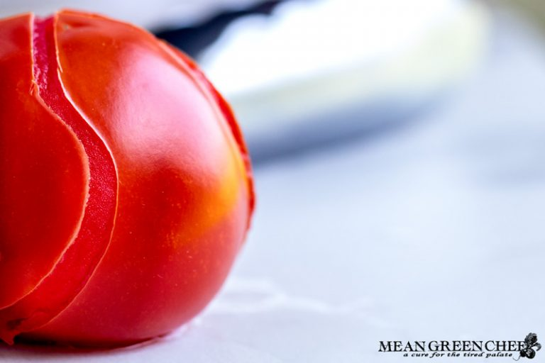 Red blanched tomato with peeling skin on white marbled counter top.