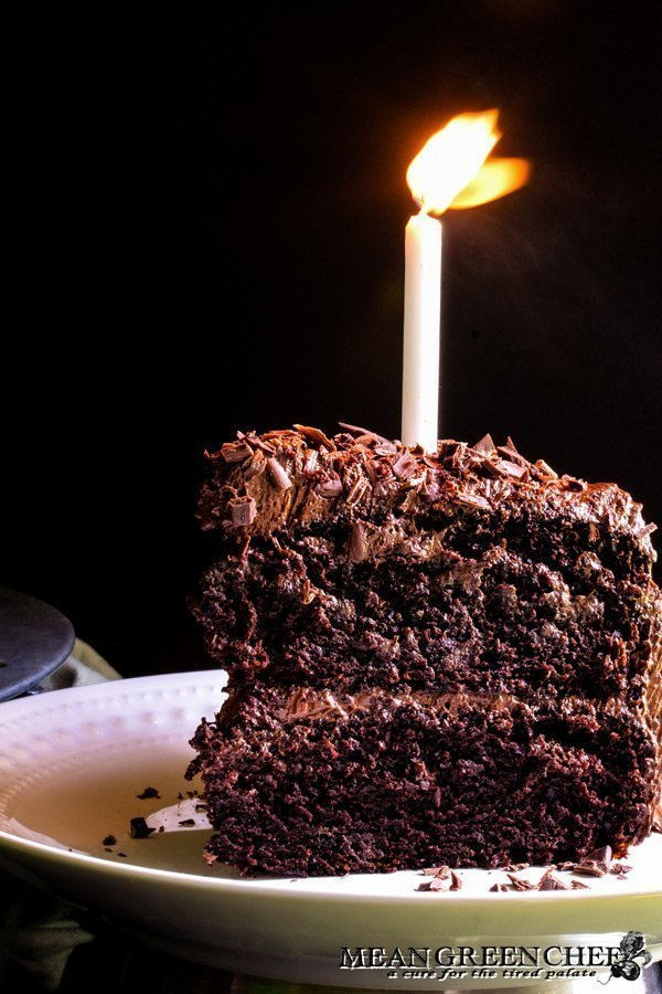 Slice of Chocolate Storm Cake with a glowing candle on top.