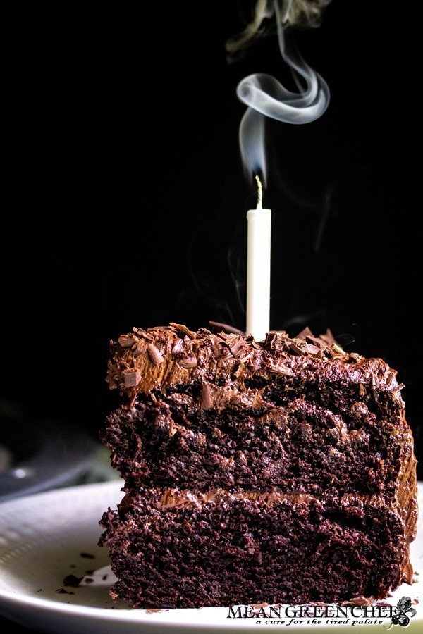 Slice of Chocolate Storm Cake with a candle that has just been blown out.