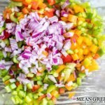 Green, red, and yellow bell peppers being tossed with a diced red onion for chicken pasta salad.