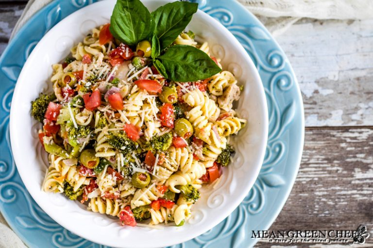 Italian Chicken Pasta Salad in a white bowl garnished with fresh basil.