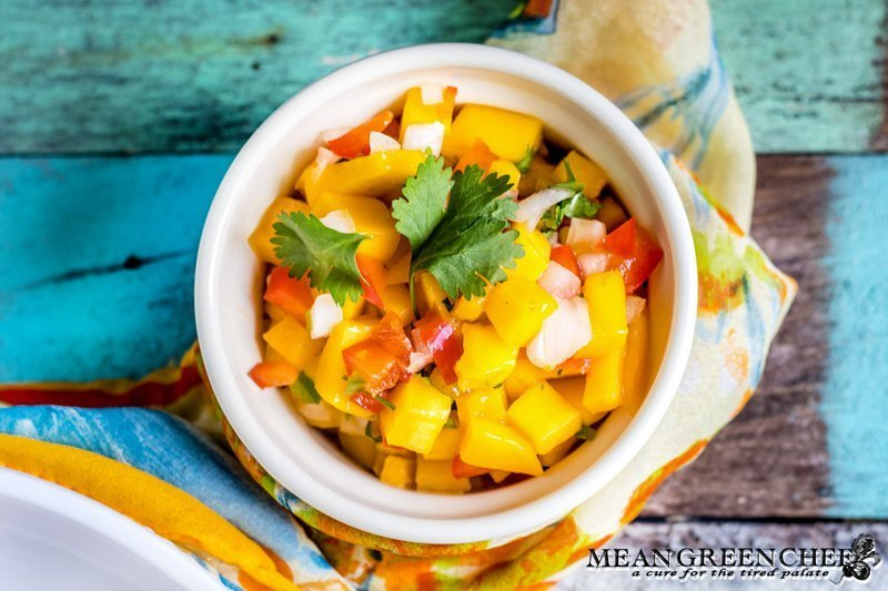 Fresh Mango Salsa in a bowl with an old blue board background.