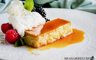 Flan on a white plate with berries and mint.